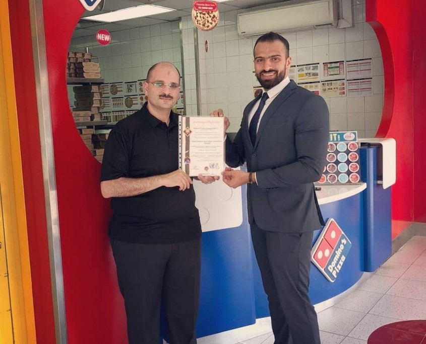 Domino's Pizza country manager Mr. Salah Shawky (left) received the HACCP certificate from H.A. Consultancies business development associate Mr. Ammar Jameel